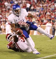 Kansas quarterback Michael Cummings is sacked by Oklahoma defensive end Rashod Favors during the third quarter on Saturday, Oct. 20, 2012 at Memorial Stadium in Norman.