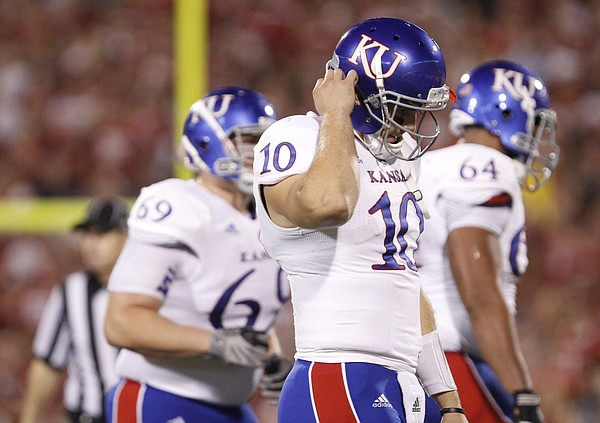 Kansas quarterback Dayne Crist unsnaps his helmet as he comes off the field during the second quarter on Saturday, Oct. 20, 2012 at Memorial Stadium in Norman.
