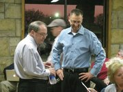 From left to right, state Sen. Anthony Hensley, D-Topeka, and Casey Moore, R-Topeka, chat with people in the crowd Tuesday night prior to the start of a forum for the 19th State Senate District race. The forum drew about 100 people at a lodge near Lake Shawnee in Topeka.