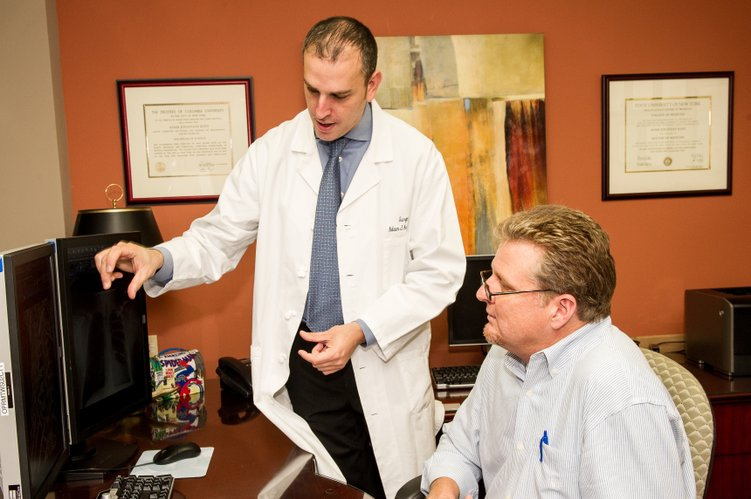 Shawnee resident Patrick Hamilton and Dr. Adam Kaye look over imaging of the titanium plates that Kaye used to fuse eight of Hamilton's ribs back together with at Overland Park Regional Medical Center following a dirt bike accident last year.