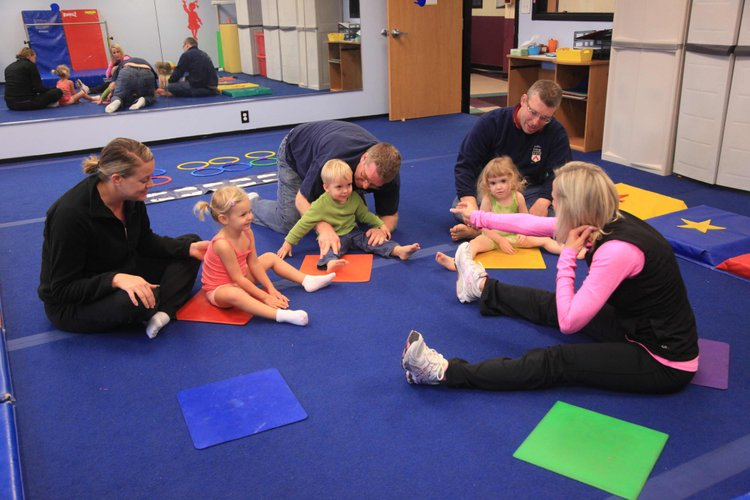 From left, Marci Ramsay and her daughter Macyn, 2, Korey Kaul and his son Eli, 2, and Landon Fulmer and his daughter Victoria, 2, get instructions from Jalon Grogan at Lawrence Gymnastics, which offers a class where parents and kids can exercise together.