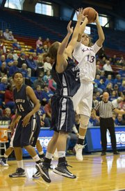 Kansas guard Monica Engelman (13) lets a shot fly over the outstretched arm of Washburn guard Laura Kinderknecht (5) during their exhibition game Sunday, Oct. 28, 2012 at Allen Fieldhouse.