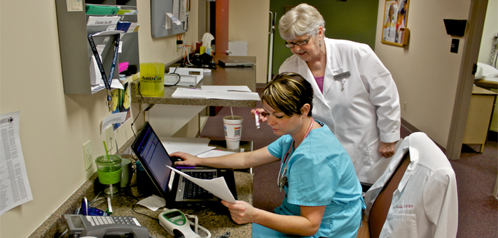 Heartland Community Health Center, a Lawrence safety-net clinic, has begun integrating mental and physical health services for its patients. Pictured here are nurse Natasha Otto, seated, and Ruby Ellis, the clinic's chief operating officer.