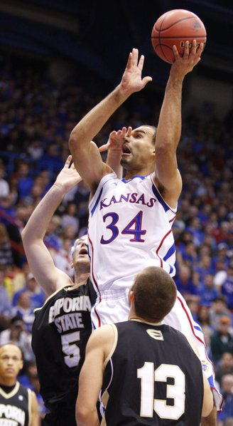 Kansas forward Perry Ellis catches a hand to the face from Emporia State forward Daniel Shaw during the first half, Tuesday, Oct. 30, 2012 at Allen Fieldhouse. Also pictured is ESU forward Michael Harris.