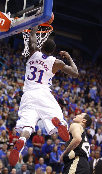 Kansas forward Jamari Traylor delivers a jam over Emporia State guard Tre Boutilier during the first half, Tuesday, Oct. 30, 2012 at Allen Fieldhouse.