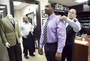 Troy Baptiste is fitted for a suit by tailors Mohan Ramchandani, right, and Bobby Kumar, left, at Mohans Custom Tailors, Jan. 31 in New York. Having a tailor mend or fit clothes can save money over buying new ones.