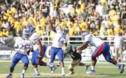 Kansas quarterback Michael Cummings heaves a pass downfield as Baylor defensive end Chris McAllister closes in during the second quarter, Saturday, Nov. 3, 2012 at Floyd Casey Stadium in Waco, Texas.