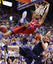 Kansas guard Travis Releford swings off the rim after a breakaway dunk as Washburn forward Christian Ulsaker crashes to the ground during the second half on Monday, Nov. 5, 2012 at Allen Fieldhouse.