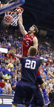 Kansas center Jeff Withey dunks as Washburn forward Bobby Chipman watches during the second half on Monday, Nov. 5, 2012 at Allen Fieldhouse.