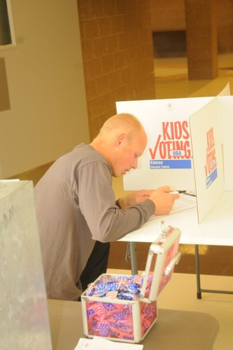 Andrew Taliaferro, a senior at Baker University, kneels at a Kids Voting station at the Baldwin Junior High School polling site to fill out his ballot Tuesday after finding all the regular voting booths filled.  Photo by Elvyn Jones