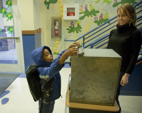Justice Rials, 5, a kindergartner at Pinckney Elementary, drops his Kids Voting ballot in the box before the start of school Tuesday, Nov. 6, 2012. At right is Kids Voting volunteer Shelli Ulmer.