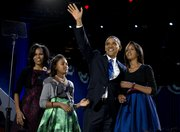 President Barack Obama waves as he walks on stage with first lady Michelle Obama and daughters Malia and Sasha at his election night party Wednesday, Nov. 7, 2012, in Chicago. Obama defeated Republican challenger former Massachusetts Gov. Mitt Romney.