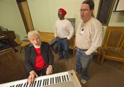After rehearsal, inmates Robert Jackson, center, and James Hansen work on their solo parts with volunteer accompanist Jo Lynn Cotton of Kansas City, Mo.