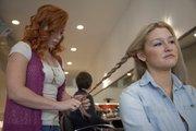 Stylist Megan Riley braids the hair of client Devon Bartel at Green Room Salon.