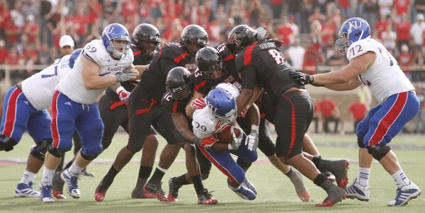 The Texas Tech defense collapses on Kansas running back James Sims during the second overtime on Saturday, Nov. 10, 2012 at Jones AT&amp;T Stadium in Lubbock, Texas.