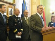 Dr. Ryan Spaulding, director of telemedicine at Kansas University Medical Center, speaks Tuesday during a news conference announcing a program to increase through telemedicine access to mental health care to military veterans. Behind from left to right are Gov. Sam Brownback, Kansas Adjutant General Lee Tafanelli, and state Rep. Tom Sloan, R-Lawrence.