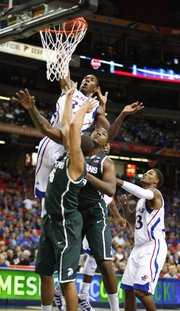 Kansas forward Jamari Traylor dunks over Michigan State defenders Derrick Nix and Denzel Valentine, front, during the first half, Tuesday, Nov. 13, 2012 at the Georgia Dome in Atlanta. At right is Kansas guard Ben McLemore.