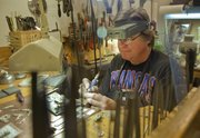 Bill Collins, of Lawrence, a jeweler and silversmith, works on some of his unique Kansas pendants Wednesday in his home studio. Collins will have pendants, pins, earrings and other jewelry for sale from 10 a.m. to 5 p.m. Sunday at the 36th annual Holiday Bazaar at the Community Building, 115 W. 11th St.
