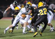 Free State running back Joe Dineen (12) looks for some yards against the Shawnee Mission West defense on Friday in the 6A state semifinals at Shawnee Mission South District Stadium.
