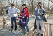 Xueying Wang, center, holding her daughter, Serenity, 7, thanks gathered Habitat for Humanity supporters and friends for help in starting her future home during a nail-drive ceremony Saturday in North Lawrence. Wang's home will be the 81st by Lawrence Habitat for Humanity. At left is Erika Zimmerman, Habitat family partner, and at right is Wang's son, Jake, 20, and her mother, Ling.