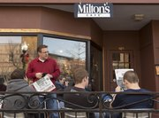 Patrons read newspapers and drink coffee in the outside dining area at Milton's as they wait to be seated Sunday, Milton's final day of business.
