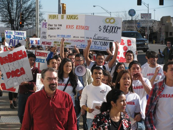 Students and their supporters on Tuesday rally against Kansas Secretary of State Kris Kobach&#39;s anti-illegal immigration policies.