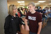 Free State swim coach Annette McDonald, left, was on hand Tuesday, Nov. 20, 2012, to watch Ben Sloan, right, sign a swimming letter of intent with UMass at FSHS.