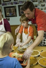 Sean Smith, Lawrence, helps his son, J.J. Smith, 10, serve pumpkin pie to another boy at the annual LINK community Thanksgiving meal served Thursday at the First Christian Church, 221 W. 10th St. J.J.'s mother and three siblings also helped serve at the event.  The Lawrence Interdenominational Nutrition Kitchen also delivered more than 400 meals.