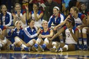 Kansas' Brianne Riley, center, is congratulated by teammates after it was announced to the crowd that the junior libero had become KU's all-time digs leader following Kansas' senior day volleyball match against Texas Tech, held Saturday, Nov. 24, 2012 at Horejsi Center. The Jayhawks made quick work of the Red Raiders, sweeping them in straight sets.