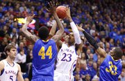 Kansas guard Ben McLemore pulls up for a shot in the lane against San Jose State defenders Alex Brown (44) and James Kinney (33) during the first half on Monday, Nov. 26, 2012 at Allen Fieldhouse. At left is Kansas center Jeff Withey.
