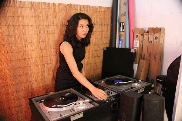 DJ Modrey Hepburn (Emily Scholle) plays music at the grand opening of Atomic Photography's new space. Photo by Racheal Major of Atomic Photography.