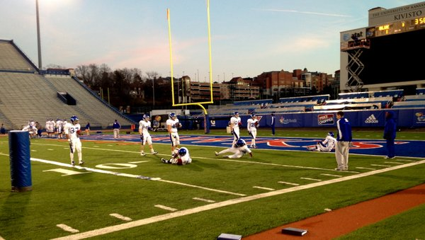 The KU running backs run through a drill at the start of Tuesday's practice at Memorial Stadium.