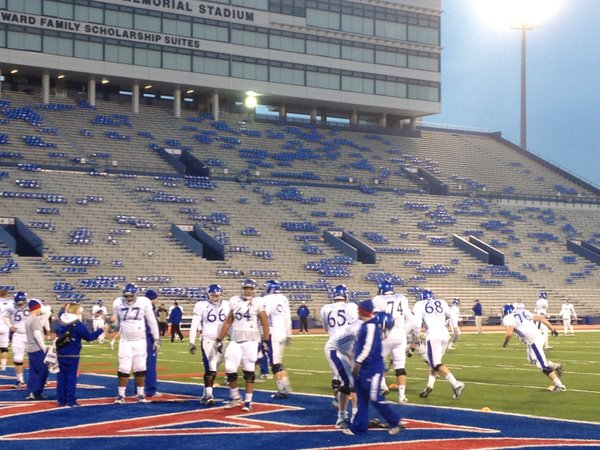 KU's offensive linemen take instructions from offensive line coach Tim Grunhard during Wednesday night's practice at Memorial Stadium.