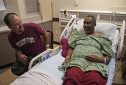 In this 2012 file photo, Rob Robinson, talks to Gillan Alexander after their kidney transplant at Kansas University Hospital in Kansas City, Kan. The men became friends five years earlier after Robinson, of Starkville, Miss., started hunting turkeys on Alexander's farm near Nicodemus, Kan. Robinson recently started a charity, Hunter Outdoors, that takes organ donors and recipients on free hunting-and-fishing excursions.