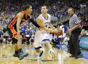 Kansas guard Evan Manning looks to pass inside against Oregon State guard Challe Barton during the first half on Friday, Nov. 30, 2012 at the Sprint Center in Kansas City, Missouri.