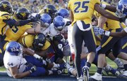 Kansas running back James Sims (29) finds an opening at the center of a pileup to score in KU's last football game Saturday against West Virginia University in Morgantown, W.Va.