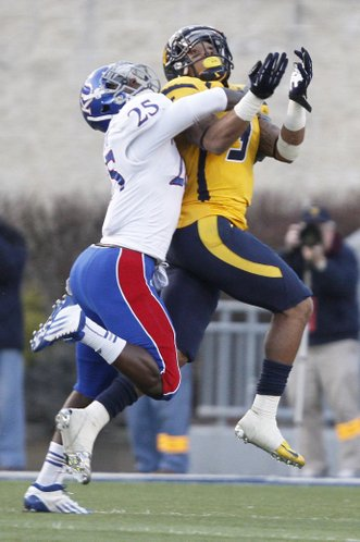 Kansas cornerback JaCorey Shepherd (25) wraps up Mountaineer receiver Stedman Bailey (3) before the ball reached him in the second half of KU's 59-10 loss Saturday against West Virginia University in Morgantown, W.Va. Shepherd was called for pass interference on the play.