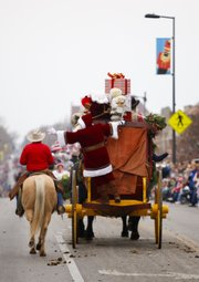 Santa Claus hangs on to the back of a buggy to end the 20th-annual Lawrence Old-Fashioned Christmas Parade on Saturday, Dec. 1, 2012.
