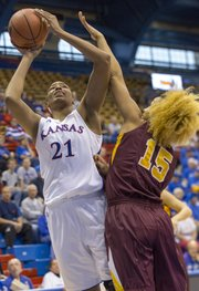 Kansas' Carolyn Davis (21) is fouled by Micaella Riche (15) while putting up a shot during Kansas' game against Minnesota Sunday afternoon at Allen Fieldhouse. The 65-53 win over the Minnesota improved Kansas' record to 7-0 on the season.