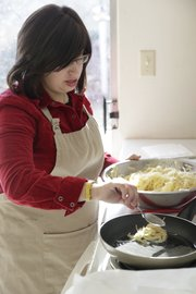 Nechama Tiechtel drops a spoonful of shredded potatoes and onions into a skillet of oil to make latkes at Lawrence's Chabad Jewish Center. Tiechtel makes latkes — a treat traditionally enjoyed during Hanukkah — the old-fashioned way, but there are also recipes for making them with zucchini or other vegetables.