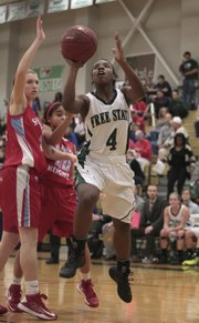 Free State senior guard A'Liyah Rogers makes a move to the basket past two Shawnee Heights defenders Friday, Dec. 7, 2012, at FSHS. The Firebirds defeated the Thunderbirds, 73-49.