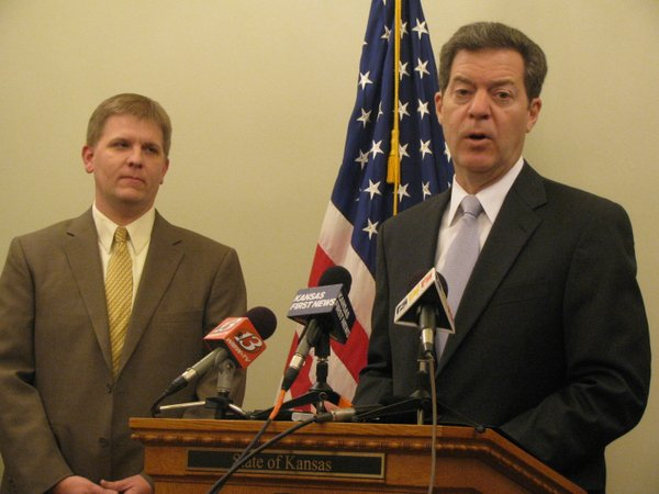 Gov. Sam Brownback announces federal approval to go ahead with KanCare. Kansas Department for Aging and Disability Services Shawn Sullivan is beside Brownback.