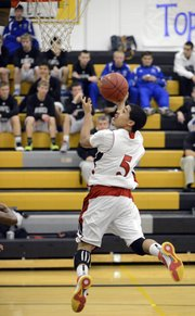 Lawrence High's Justin Roberts goes up for two after a steal and fast break Friday, Dec. 7, 2012, at Blue Valley High.