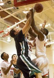 Free State's Blake Winslow, left, and Joe Henry battle on the boards for a rebound during Free State's match up against Lansing, Saturday, Dec. 8, 2012 in Lansing.