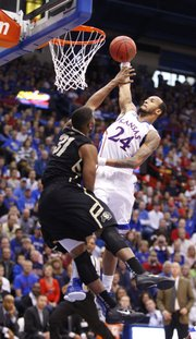 Kansas guard Travis Releford extends to dunk over Colorado defender Jeremy Adams during the first half on Saturday, Dec. 8, 2012 at Allen Fieldhouse.