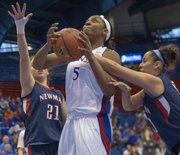 Kansas' Bunny Williams (5) is fouled by Brianna Caldwell, right, as she splits a double team of Caldwell and Alexandra Ciabattoni (21) during Kansas' game against Newman, Sunday, Dec. 9, 2012 in Allen Fieldhouse. Kansas won 97-64.