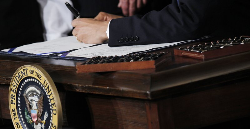 Charles Dharapak/AP File Photo  This March 23, 2010, file photo shows 22 pens next to President Barack Obama as he signs the health care reform bill in the East Room of the White House in Washington. Multiple pens are used to sign legislation, and then distributed to supporters of the legislation. Your medical plan is facing an unexpected expense, so you probably are, too. It's a new, $63-per-head fee to cushion the cost of covering people with pre-existing conditions under President Barack Obama's health overhaul. The charge, buried in a recent regulation, works out to tens of millions of dollars for the largest company health plans, and much of that is likely to be passed on to employees.