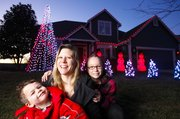 "Lawrence mother Stephanie Fisher is pictured with her two children, Noah, 4, and Kaitlyn, 10, in front of their home at 909 Stonecreek Drive. Fisher and her husband, Kent, have put up their Christmas display for years, but this year they've included an option for passersby to show their appreciation by donating to charity. Those choosing to do so can text ""justfood"" to 80888 to make a $10 donation to the food bank."