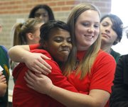 Free State High seniors A'Liyah Rogers, left, and Courtney Parker hug after signing their national letters of intent on Wednesday, Dec. 12, 2012, in the commons area at Free State High. Rogers will be playing softball for Bradley University while Parker will be playing for Benedictine College.