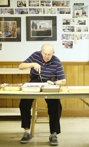 "West Side Presbyterian volunteer Arden Burgess, ""the cake man,"" slices pieces of cake before lunch at the Lawrence Interdenominational Nutrition Kitchen (LINK), Thursday, Dec. 13, 2012."
